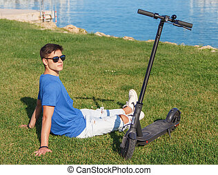 Young Caucasian man sitting on grass near electric scooter
