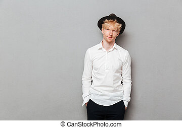 Young caucasian man standing isolated over grey wall