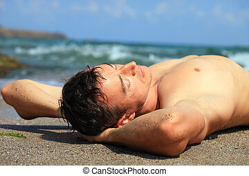 Young caucasian man sunbathing at a beach - Closeup view of ...