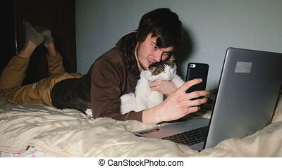 Young Caucasian man taking a selfie with the cat on smartphone lying on bed in front of laptop.