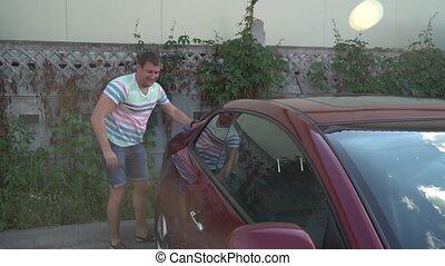 Young caucasian man washing his car on the car wash self-service. Car washing.