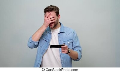 Young caucasian man winner hold smartphone feel amazed overjoyed with mobile online bet bid app game.