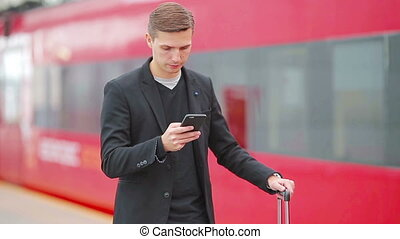 Young caucasian man with smarphone and luggage at station traveling by train