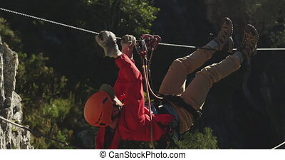 Young Caucasian man zip lining - Side view of a Caucasian...