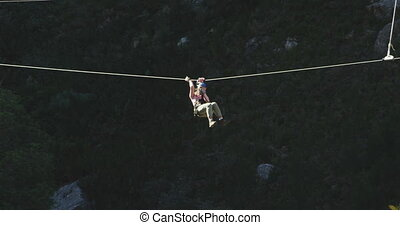 Young Caucasian man zip lining - Side view of a young...
