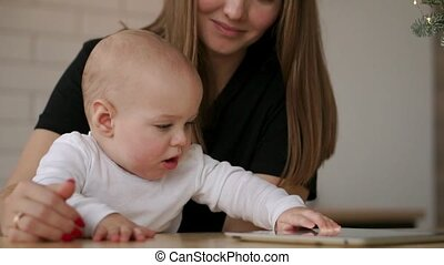 Young Caucasian Mother using Tablet with her Baby son. Slow ...