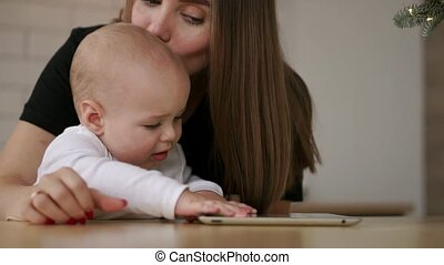 Young Caucasian Mother using Tablet with her Baby son. Slow...