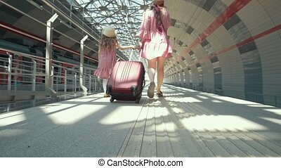 Young caucasian mother with suitcase and her little daughter walking at the railway station