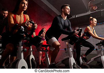 young caucasian people exercising, legs cardio training on bicycle in fitness gym