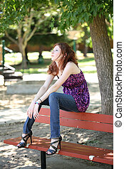Young caucasian teen girl sitting on park bench