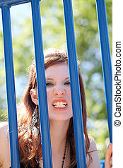 Young caucasian teen girl snarling through bars