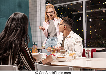 Young Caucasian woman arguing with her boyfriend while he sitting with another girl.