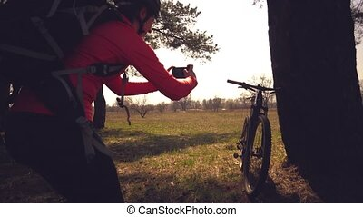 Young caucasian woman athlete tourist cyclist makes photo on...