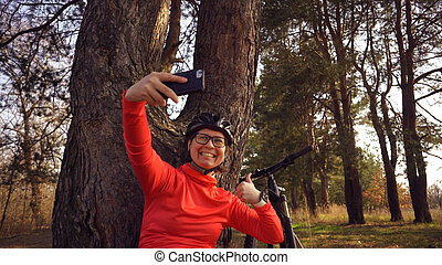 Young caucasian woman athlete tourist cyclist uses hand smart phone photo of herself selfie sitting near tree in coniferous forest outside the city. Sportswoman taking selfie with her mountain bike