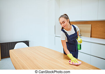 Young caucasian woman cleaning kitchen