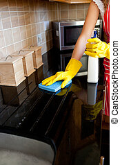 Young caucasian woman cleaning the oven in the kitchen