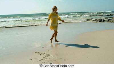 Young Caucasian woman dancing on the beach 4k
