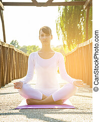 Young caucasian woman doing yoga in park at sunset.