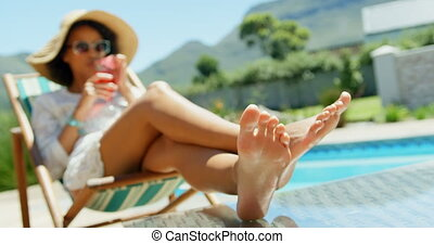 Young Caucasian woman drinking cocktail drink near swimming ...