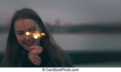 Young caucasian woman having fun with sparkler at sunset outdoors