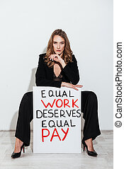 Young caucasian woman holding blank with text about work - ...