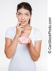 Young caucasian woman holding tasty donut