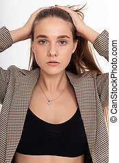 young caucasian woman in black top and suit jacket isolated on white background