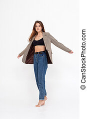 young caucasian woman in black top, blue jeans and suit jacket isolated on white