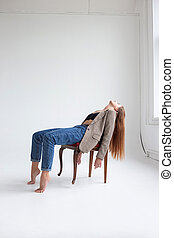 young caucasian woman in black top, jeans, suit jacket, lying on chair at studio