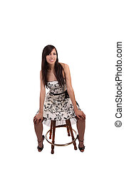 Young caucasian woman in dress on stool