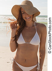 Young Caucasian woman in hat and bikini looking at camera