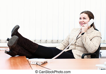 Young caucasian woman in office interior calling by telephone. Legs on a table. Office life