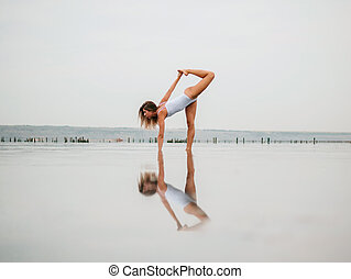 Young caucasian woman in swimsuit practicing yoga in water liman, lake or river. Beautiful reflection. Complex asanas, balance. Fitness, sport, yoga and healthy lifestyle concept.