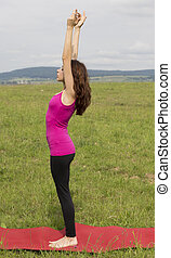 Young woman is doing Upward Salute pose outdoors.