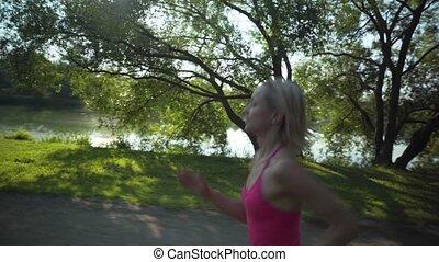 Young caucasian woman jogging in public park near the river