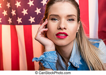 young caucasian woman looking at camera in front of USA flag, Independence Day of America