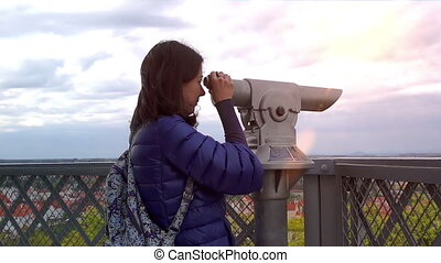 Young caucasian woman looks to the binoculars at the sunset,...