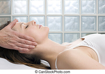 young caucasian woman lying down receiving head massage