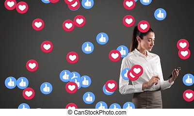 Animation of hearts and like emojis floating over Caucasian woman using a smartphone on grey background. Global economy and technology concept digital composite