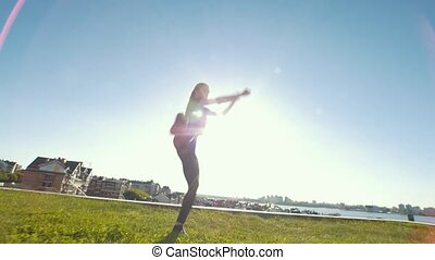 Young caucasian woman performs acrobatic jumps outdoors at sunny day