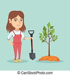 Young caucasian woman planting a tree.