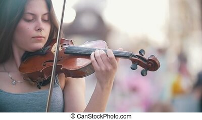 Young caucasian woman playing a fiddle on pedestrian street...