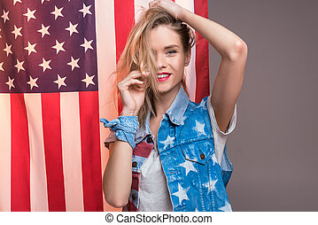 young caucasian woman posing in front of USA flag, Independence Day of America