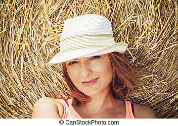 Young caucasian woman posing with haystack
