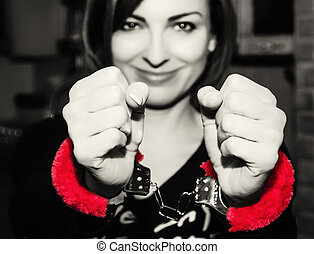 Young caucasian woman posing with red handcuffs at the party