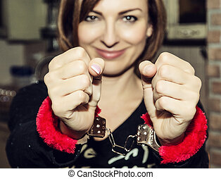 Young caucasian woman posing with red handcuffs, photo filter