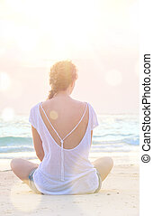 woman practicing yoga at sunrise beach
