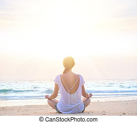 woman practicing yoga at sunrise beach