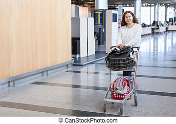 Young Caucasian woman pulling luggage hand-cart in airport hall
