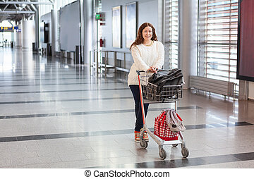 Young Caucasian woman pulling luggage hand-cart with bags along airport hall. Passenger in waiting area.